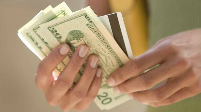 woman's hands hold cash and credit card