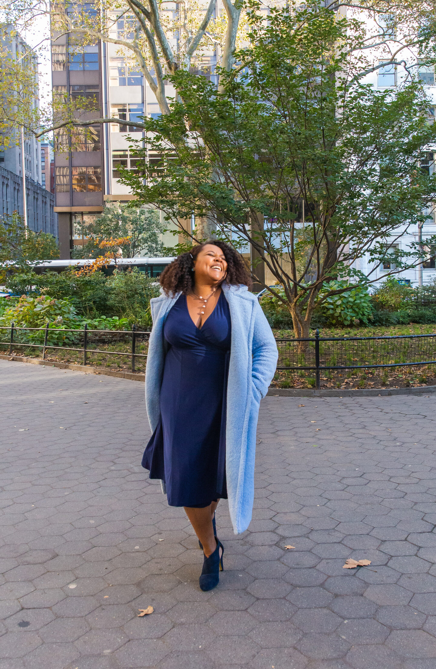 patranila walks in madison square park wearing blue dress and coat