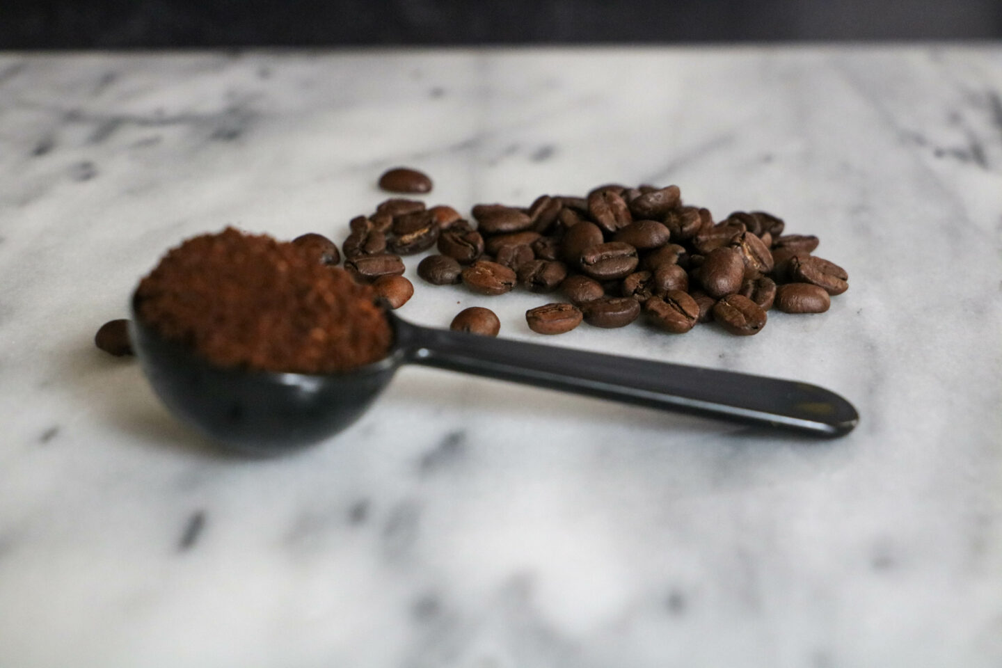 rich kona coffee beans with scoop of grounds