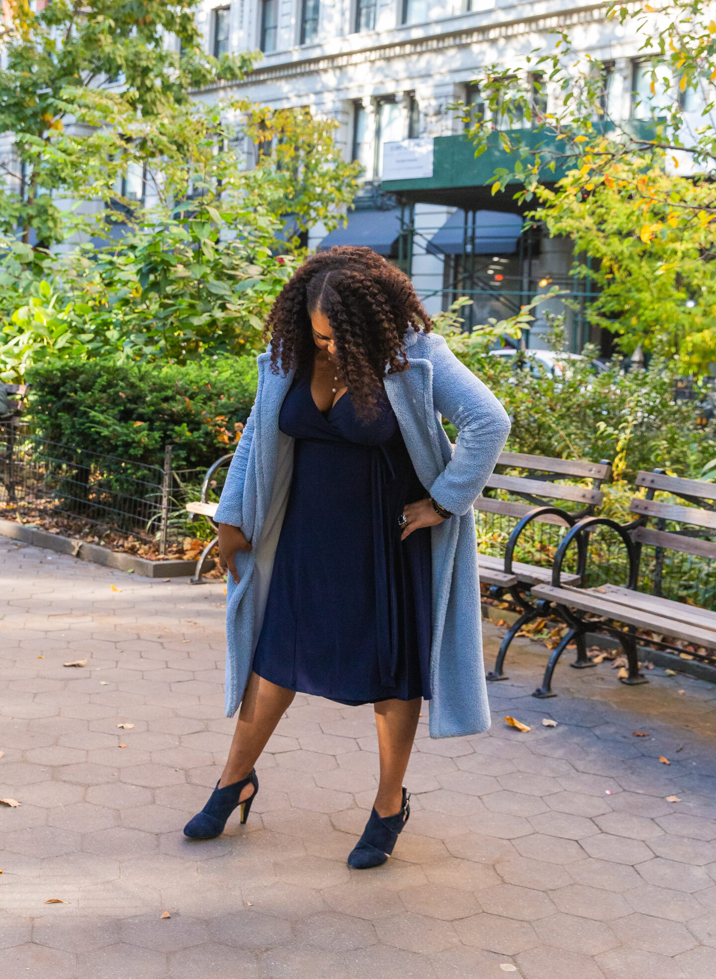 patranila wears blue wrap dress by kiyonna and blue teddy coat by something navy
